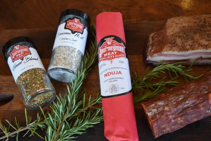 stylized photo of two spice jars, pancetta, and a chub of each Nduja and Pepperoni